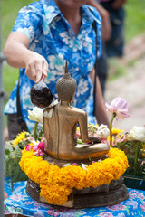 Water is pouring to Buddha statue for worship .