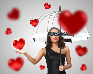 Pretty young woman with umbrella and hearts