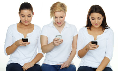 Three girls are sending an SMS on white background