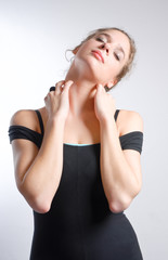 Young beautiful blonde woman in fitness clothing & hands on neck