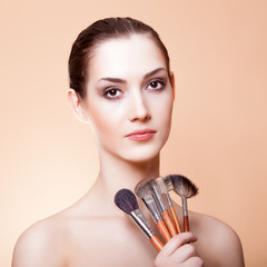portrait of beautiful woman with makeup brushes