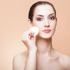woman cleaning her face with cotton sponge