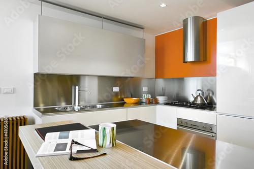Cucina moderna con alzata di acciaio e muro arancione for Abbonamento a cucina moderna