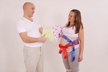 Man and pregnant woman holding baby clothes