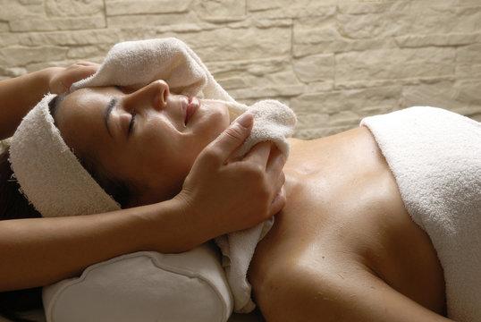 Joven mujer recibiendo tratamiento facial en un spa.