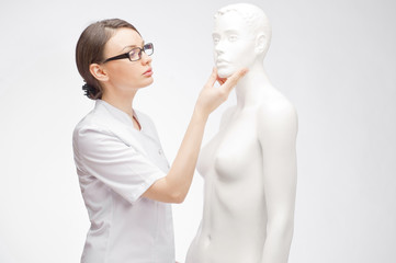 Female medical doctor student training with fake patient
