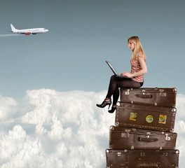 Beautiful blond girl sitting on suitcases above clouds