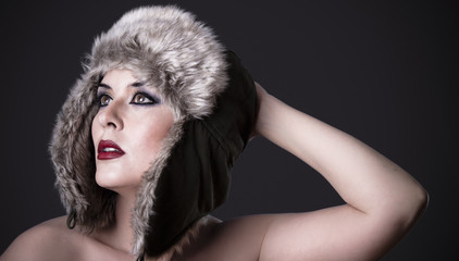 Female green-eyed brunette with fur hat, winter concept