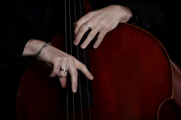 Contrabass player in front of black background