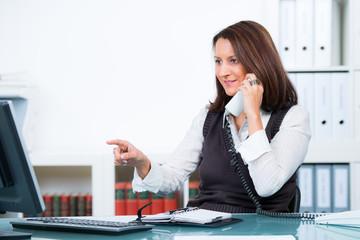 geschäftsfrau führt telefongespräch und zeigt auf den bildsch