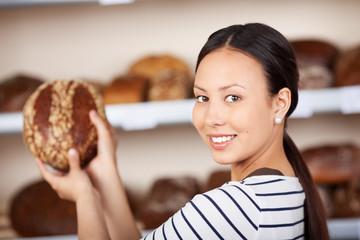 lächelnde bäckereiverkäuferin mit brot