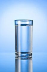 glass of pure water on blue glossy background