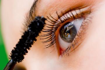 Beautiful woman applying mascara on her eye with brush