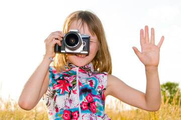 little girl taking picture with SLR camera