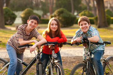 Two teenage boys and one teenage girl having fun on bicycles