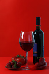 Red wine on red background with red fruit and vegetabe