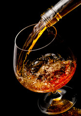 Fototapete - The glass with splashes cognac