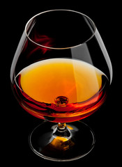 Fototapete - cognac in glass isolated on black background