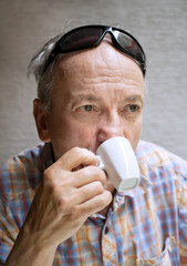 old man drinking cup of coffee