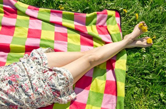 Beine einer jungen Frau im Sommerkleid auf Picknick-Decke auf einer grünen Wiese