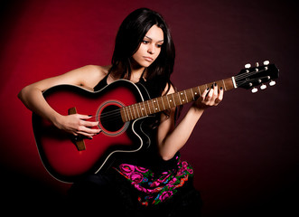 Carmen beautiful woman with guitar on dark background