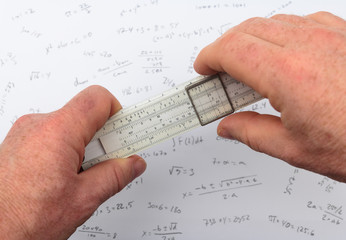 person calculating on a slide rule