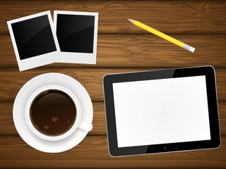 Coffee cup, photo frame and tablet pc on wooden background.
