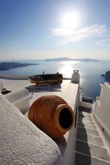 Spoed Fotobehang Santorini Santorini with vase and boat on white roof, Greece