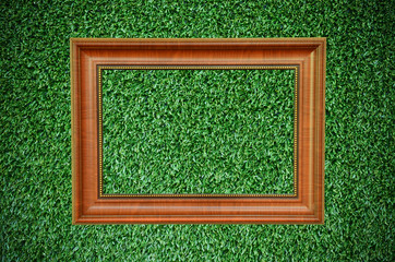 Vintage wood picture frame on beautiful deep green grass texture