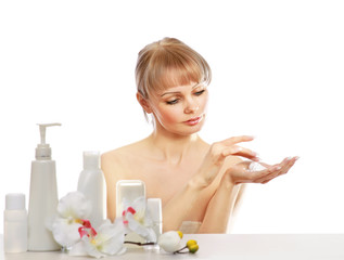 A young woman applying cream on her skin