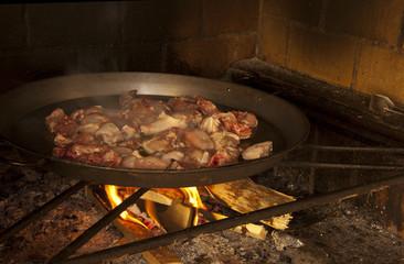 Friendo pollo y conejo para hacer paella valenciana