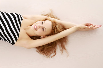 Smiling pretty woman stretching on the floor