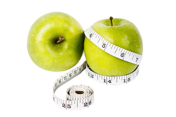 Dieting concept Green apples with measuring tape