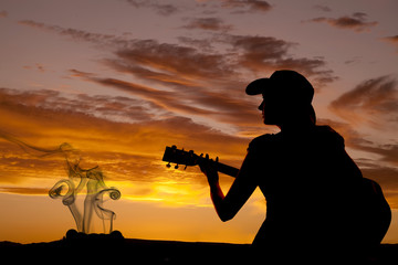 Silhouette woman guitar by fire