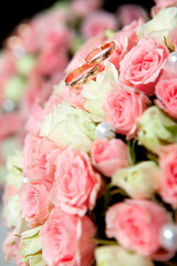 wedding rings of the groom and the bride on a bunch of flowers.