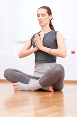 Woman doing stretching yoga exercise at sport gym