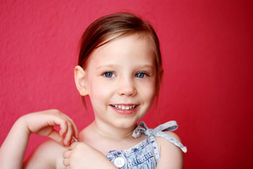 smiling cute little girl over pink background