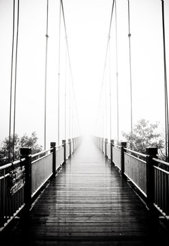 view on pedestrian wooden bridge in mist