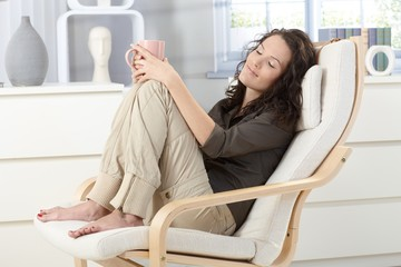 Woman relaxing in armchair