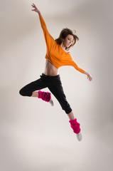 A young Caucasian female dancer caught in a jump