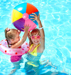 Child playing with ball in swimming pool.