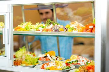 Cafeteria food display young man choose salad