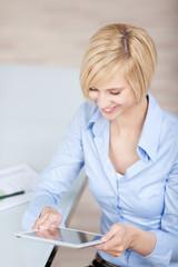 blonde geschäftsfrau schaut auf tablet