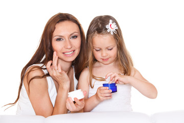 Mother and daughter with cream