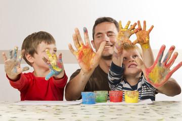 Vater malt mit seinen Kindern mit Fingerfarbe