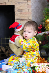 small boy with gift near fir trees