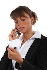 Woman with telephone and business card