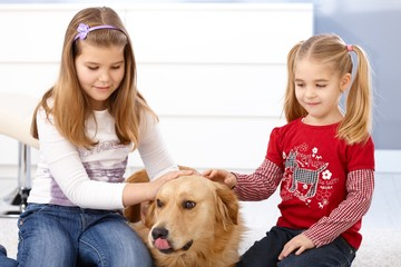 Little girls stroking dog smiling