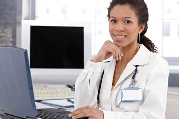 Smiling ethnic doctor with laptop computer