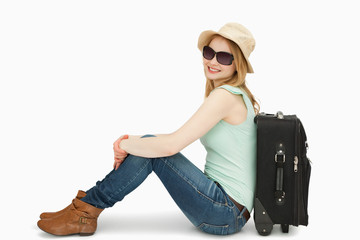 Woman wearing sunglasses while sitting near a suitcase